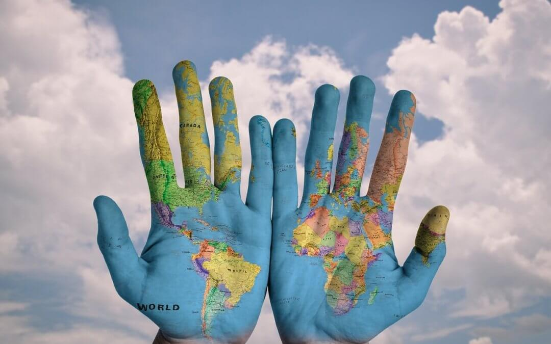 hands painted with world map. I want to move abroad. where do i start?