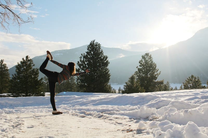 Woman in snow doing yoga pose with sun rays