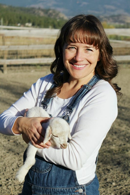 pretty brunette in overalls holding a baby goat