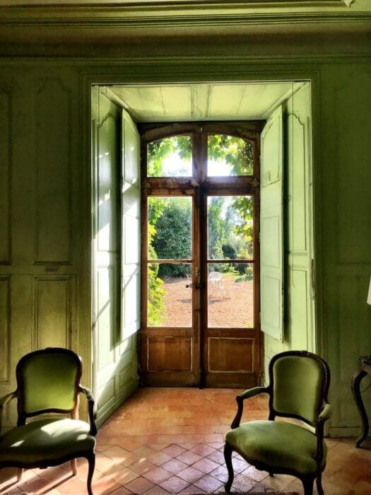 green walls and chairs looking out to gardenfrench lifestyle