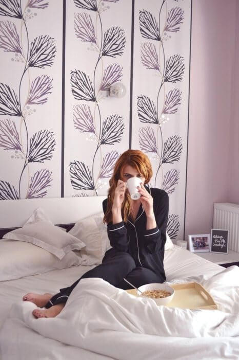 Girl in bed with black pjs drinking coffee