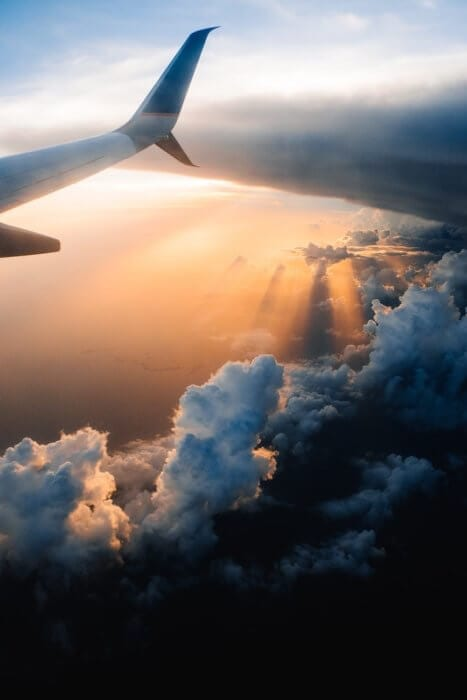 Sun rays and wing from a plane window. Moving to Malaysia