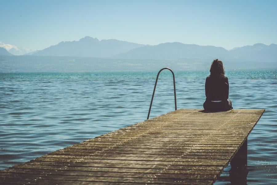 girl sitting on pier-moving away from family