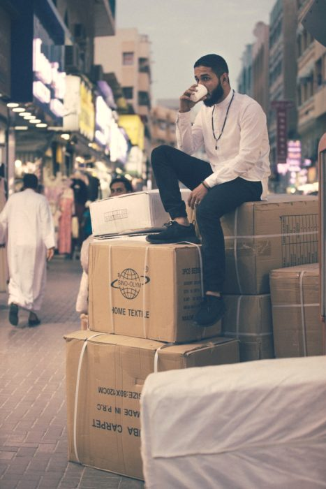 guy sitting on top of boxes: checklist for moving abroad