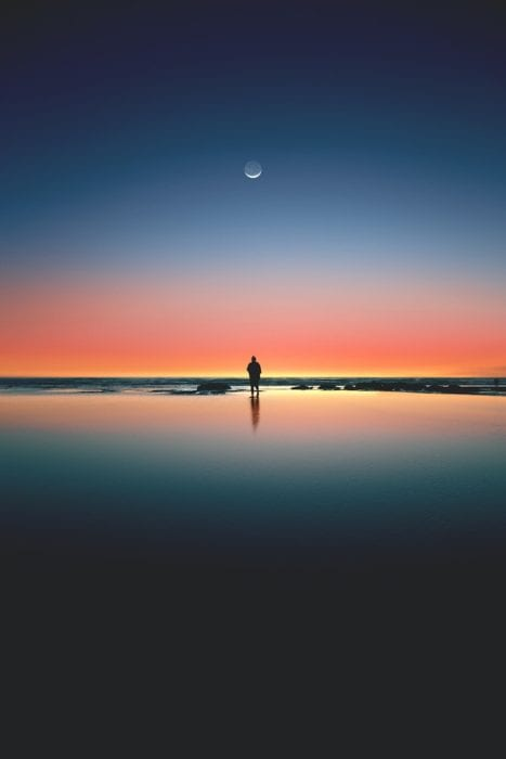 shadow of man at sunset below the moon