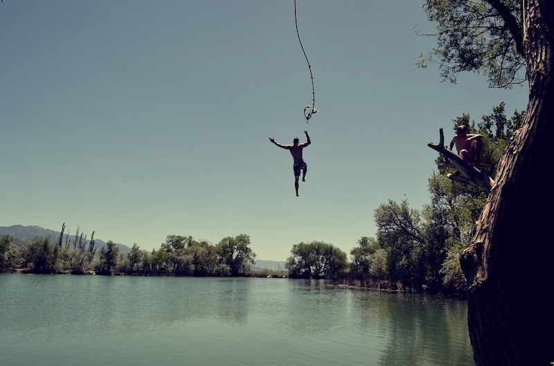 guy letting go of rope swing over water.