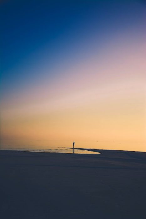 moving away from family can be lonely. person alone on the beach at sunset