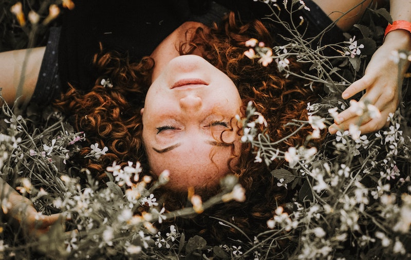 redhead laying in the flowers: move away from family