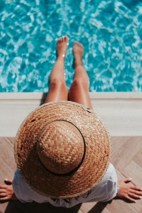 girl with hat by pool